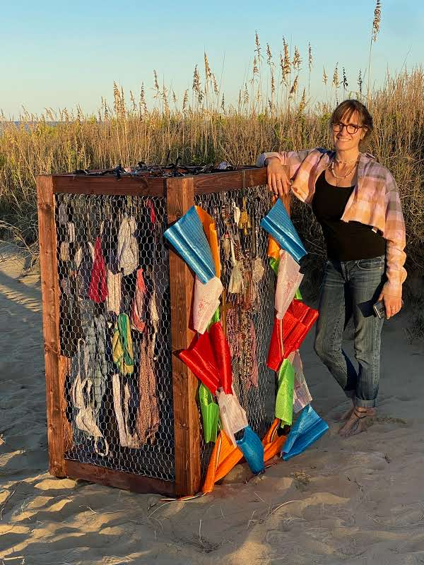 Artist standing on a beach next to a large crate containing clothing with fabric on the outside.