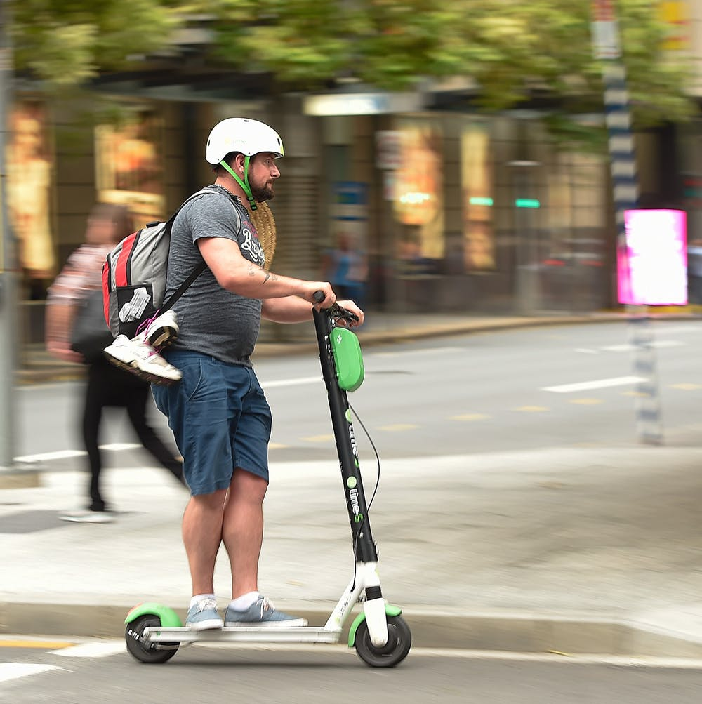 An adult rides an electric scooter