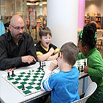 adult and children playing chess